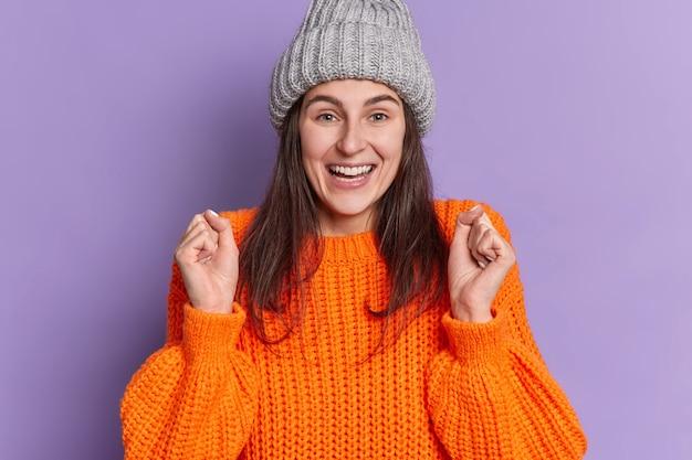 ポジティブなブルネットの白人女性は、くいしばられた握りこぶしを上げます笑顔は、ニットのセーターの帽子をかぶって、非常に良いことが起こるのを前向きに待っています。