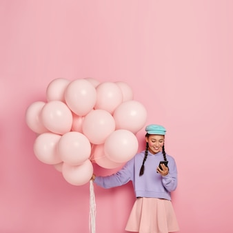 Positive brunette girl types messages on mobile phone, surfs internet, carries helium balloons
