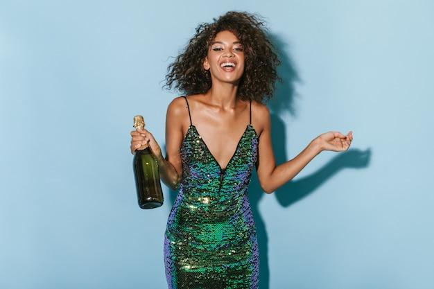 Позитивная брюнетка с классным макияжем в современном зеленом платье смеется и держит бутылку с напитком на изолированной стене.