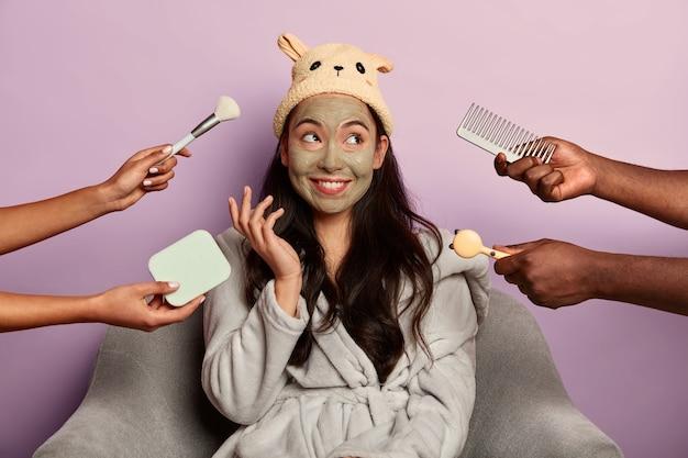 긍정적 인 갈색 머리 아가씨는 안락 의자에 앉아 클레이 마스크로 얼굴을 청소합니다.