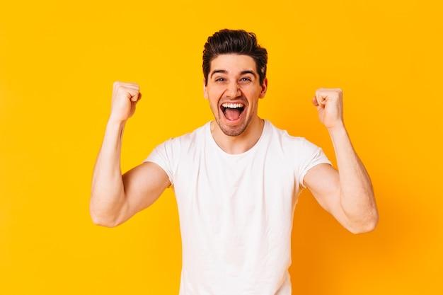 긍정적 인 갈색 머리 남자는 승리에 기뻐합니다. 주황색 공간에 흰색 티셔츠에 남자의 초상화.