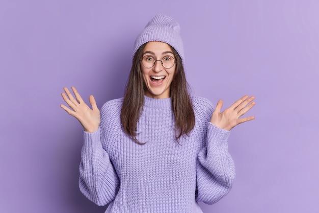 ポジティブなブルネットのミレニアル世代の女の子は、手のひらを上げて、何か素晴らしいものに反応します。帽子とセーターを着てとても幸せです。
