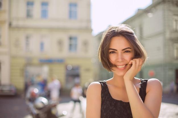 청동 황갈색과 자연스러운 화장을 한 긍정적인 갈색 머리 모델이 거리를 걷고 있습니다. 텍스트를 위한 공간