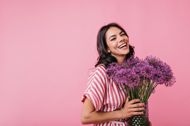 Positive brunette with dimples radiates joy. snapshot of cute curly lady with lovely huge purple flowers.