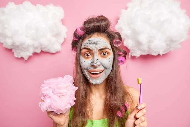 Positive brunette woman applies hair rollers for making hairstyle holds shower sponge brushes teeth with brush has nourishing clay mask on face isolated over pink wall