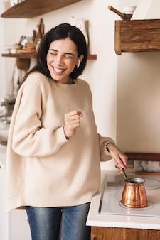 キッチンのプレートにステンレス鋼トルココーヒーポットでコーヒーを淹れるポジティブブルネットの女性