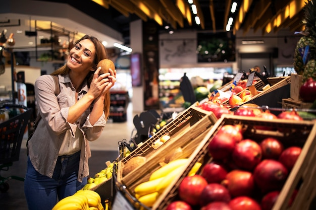 Positive brunette woman holding coconut at grocery store fruit department