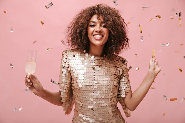 笑顔とピンクの壁に紙吹雪とワインとガラスでポーズをとってモダンなベージュのドレスでポジティブなブルネットの女性。