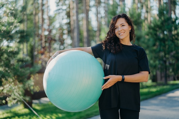 Positive brunette woman leads active lifestyle holds fitness ball poses against forest