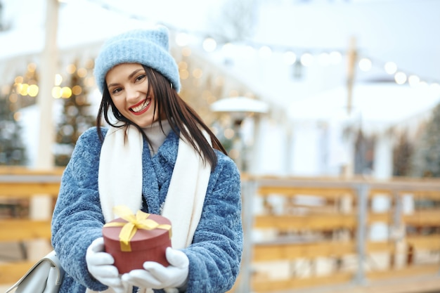 Positive brunette woman in winter coat holding a gift box at christmas fair. space for text
