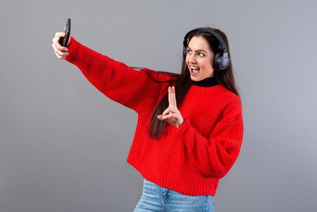 Позитивная брюнетка в наушниках, одетая в красный свитер, делает селфи со смартфоном, изолированным на сером