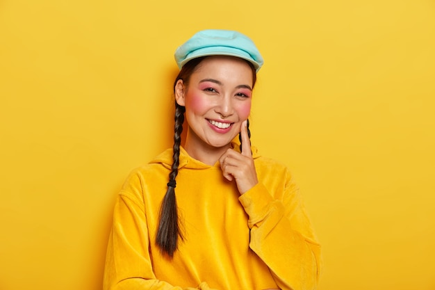 Positive brunette woman with healthy complexion, touches rouge cheek with index finger, smiles happily, dressed in casual yellow hoodie