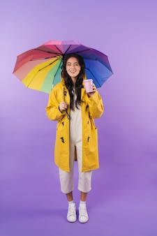 Positive brunette woman in yellow raincoat posing isolated over purple wall wall holding umbrella and coffee.