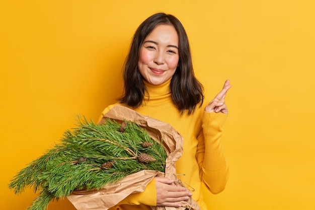 ポジティブなブルネットの若い女性は、新年に家を飾るためにスプルースグリーンの花束を運び、願い事をし、クリスマスの作曲を準備するために指を交差させます