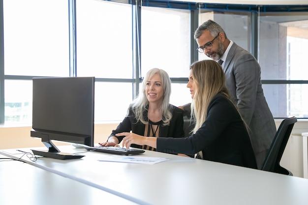 Pcモニターでプレゼンテーションを見たり、プロジェクトについて話し合ったり、職場に座ったり、ディスプレイを指さしたりする前向きなビジネス仲間。ビジネスコミュニケーションの概念