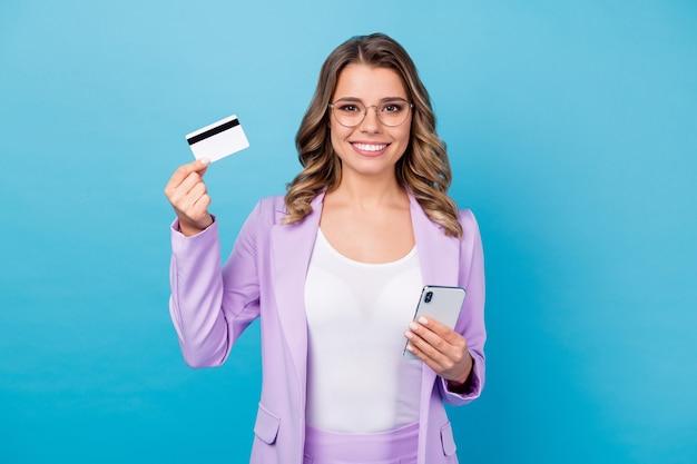 Позитивная бизнес-леди использует кредитную карту смартфона, изолированную на синем цвете