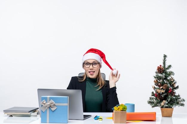 Donna positiva di affari che gioca con il suo cappello di babbo natale seduto a un tavolo con un albero di natale e un regalo su di esso e sporge la lingua su sfondo bianco