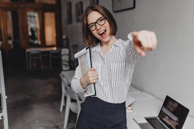 ポジティブなビジネスウーマンは笑顔でカメラに指を向けます。ズボンとブラウスの女性は、オフィスの背景にドキュメントでポーズします。