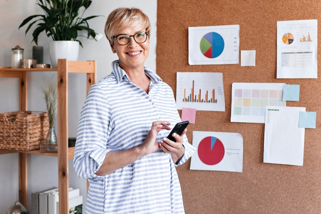 Positive business woman in striped shirt holds smartphone