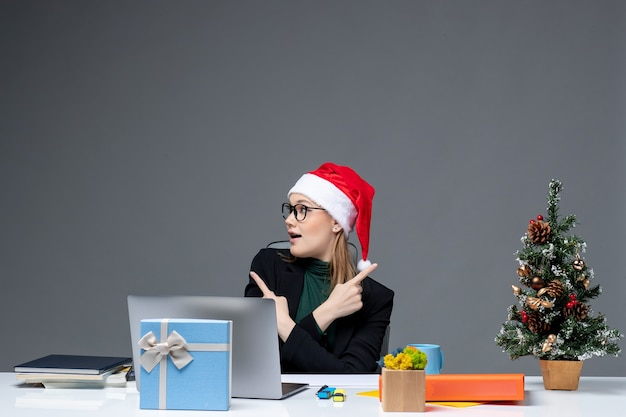 Positive business woman with santa claus hat sitting at a table with a xmas tree and a gift on it on dark background
