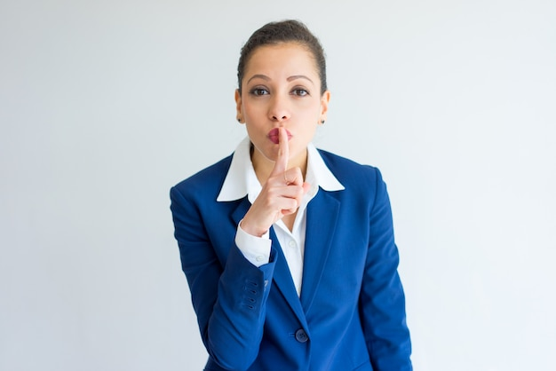 Positive business woman with shh gesture.
