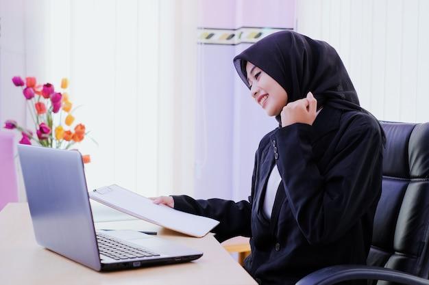 Позитивная деловая молодая женщина, веселая в офисе, получает новую идею, держа финансовый отчет о работе