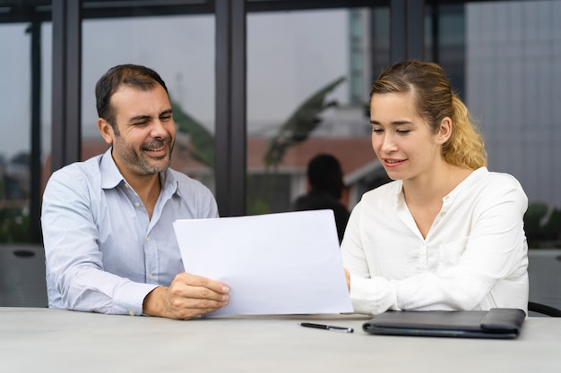 Positive businessman asking expert to check documents
