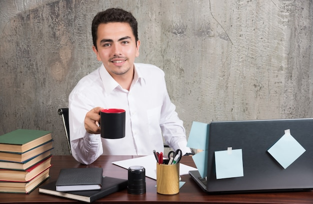 Положительный бизнесмен, держа чашку чая за офисным столом.