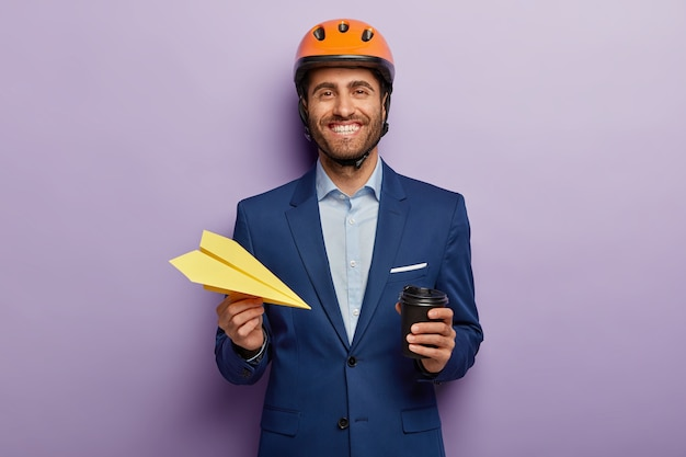 Positive businessman posing in classy suit and red helmet at the office