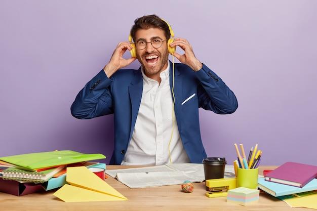 Imprenditore positivo seduto alla scrivania in ufficio