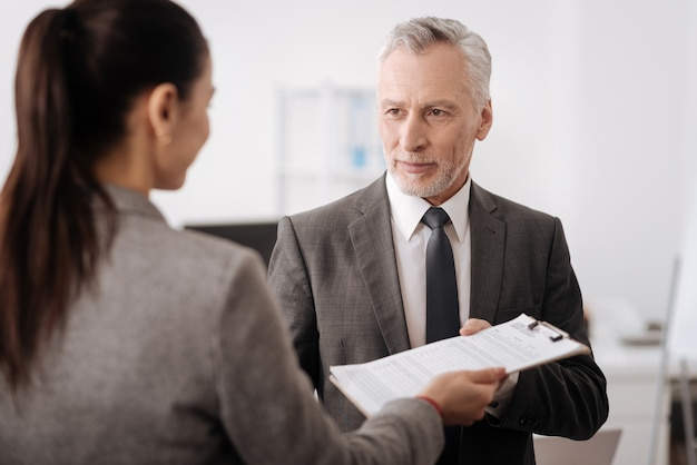 Positive businessman wearing smart clothes looking sideways while having meeting with his coworker
