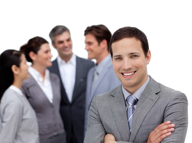 Positive businessman with folded arms standing with his team