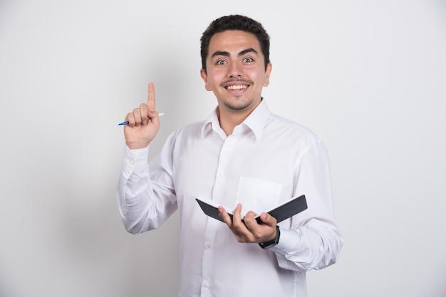 Imprenditore positivo con il taccuino e la penna rivolta verso l'alto su sfondo bianco.