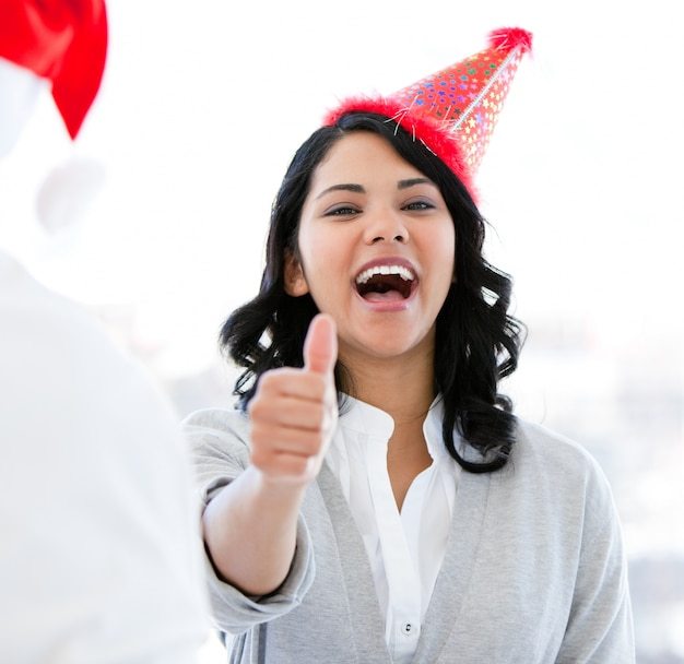 Positive businesswoman doing a thumb-up to celebrate christmas
