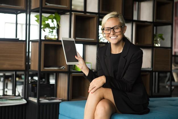 Positive businesswoman showing digital tablet