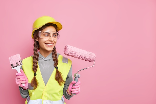 Positive busy female builder involved in renovation and repair of building holds roller and paint brush follows strict safety regulations wears protective equipment has leadership skills. copy space