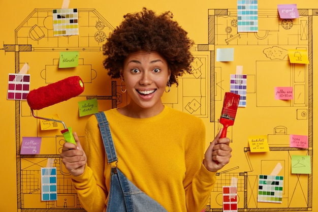 Positive busy female painter holds paint roller and brush, does house repairing, dressed in yellow jumper and overalls