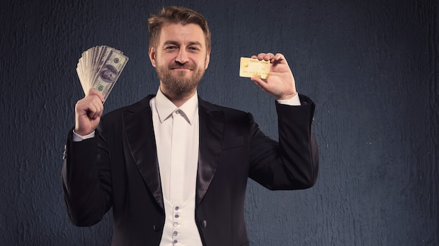 Positive butler man in a tailcoat offers a credit card and money.