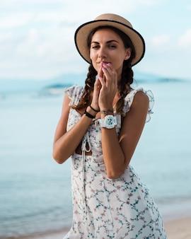 Donna calma positiva in abito estivo leggero, cappello di paglia, posizione tropicale