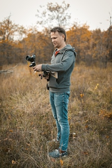 写真とビデオのコンテンツを撮影するためのデジタルスタビライザーでカメラを準備している肯定的なカメラマン