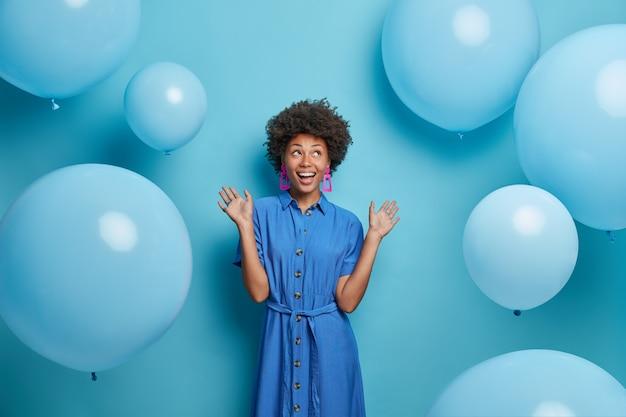 La donna afroamericana spensierata positiva pronta per la celebrazione, vestita in abiti festivi, pone contro palloncini blu