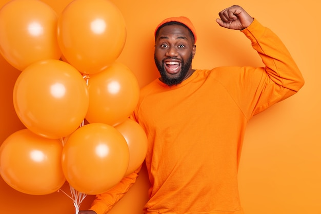 Positive carefree black man raises arm has overjoyed expression enjoys party celebration smiles broadly holds inflated balloons poses against orange wall has fun comes on friends birthday