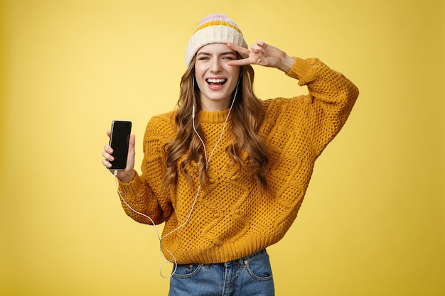 Positive carefree charming young girl show peace gesture wearing wired earphones showing smartphone screen promoting app cool brand new mobile phone, laughing carefree yellow background