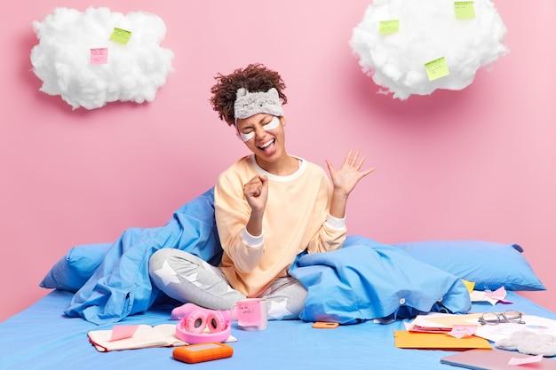 Positive carefree dark skinned curly woman sings songs in bed does homework