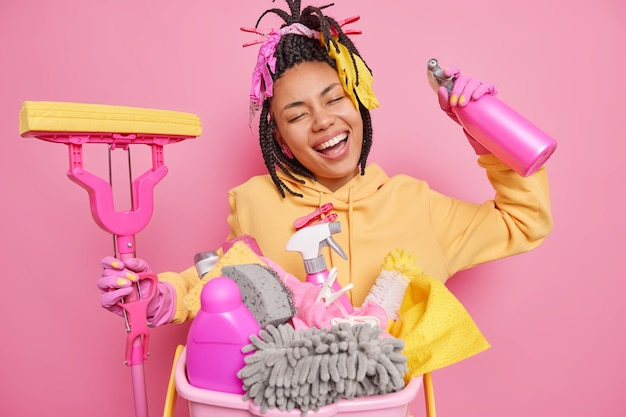 Positive carefree ethnic housewife with happy smile holds cleaning detergent and mop