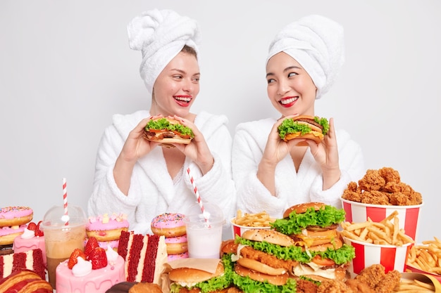 Positive carefree female friends look gladfully at each ther while eat delicious sandwiches prefer eating fast food