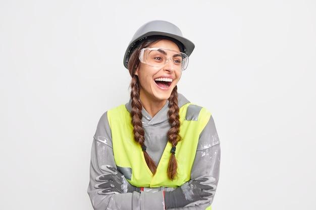 積極的な屈託のない女性エンジニアが喜んで笑い、腕を組んで目をそらし、迅速な建設作業に満足