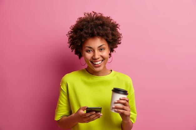 Positiva donna spensierata con acconciatura afro tiene tazza di caffè usa e getta, invia messaggi di testo, naviga in internet, vestita casualmente,