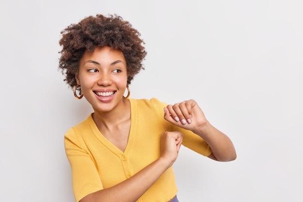 ポジティブなのんきな若いアフロアメリカ人女性が腕を振る白い壁に隔離された黄色のジャンパーに広く身を包んだ笑顔