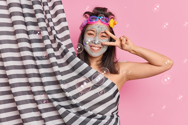 Positive carefree young woman makes peace gesture over eye smiles gladfully applies clay mask enjoys showering applies hair curlers isolated over pink background with soap bubbles falling down